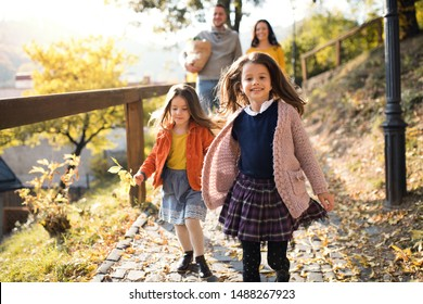 Two girls with unrecognizable parents in the background walking in park in autumn.