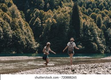 Two girls Wade cross the mountain stream