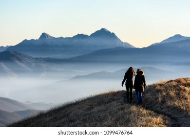 two girls walk on high altitude trail in the mountains