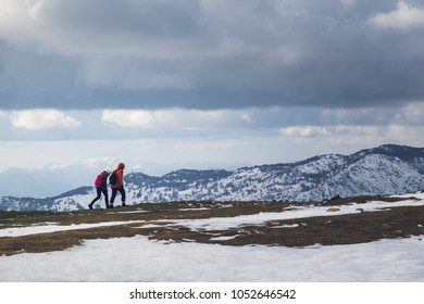 Two girls walk at the top of mountain with snow