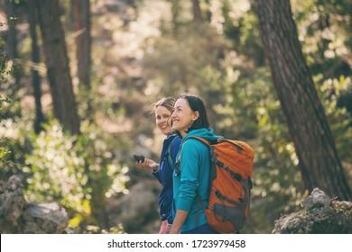 Zwei Mädchen gehen im Wald spazieren.Wandern in den Bergen. Freundinnen verbringen Zeit in der Natur zusammen. Frauen gehen im Park spazieren.