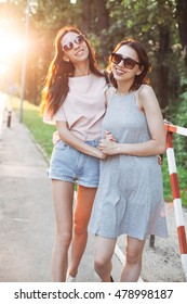 Two girls walking along a road at sunset and smiling.