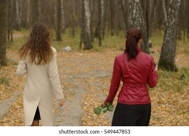 Two girls walking in the autumn forest