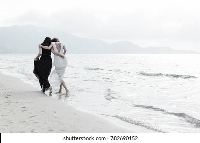 Two girls walking near se on the beach. Back view of happy sisters or best friends.