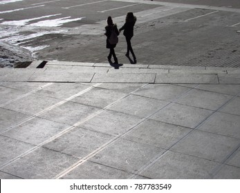 two girls are walking on the gray street