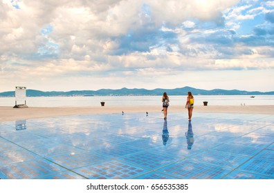Two girls walking on top of Sun Salutation installation made of solar photovoltaic cells near the sea shore against the background of a hill range and dramatic cloudy morning sky. Zadar, Croatia