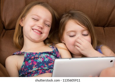 Two girls watching a tablet and laughing