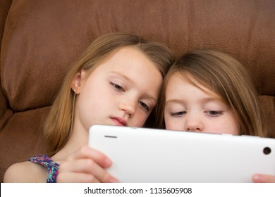 Two girls watching a tablet together
