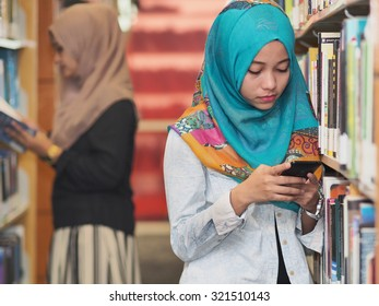 Two girls wearing hijab in a library.