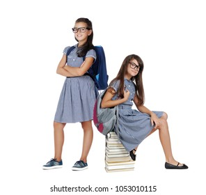 Two girls wearing school uniform and glasses isolated on white