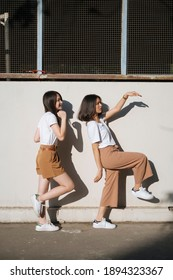 Two girls in white t-shirt and brown pants do the silly act together in the sunlight at the wall.
