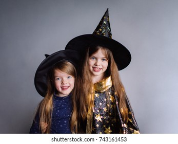 two girls in witch costumes and in hats at a Halloween party