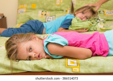 Two girls woke up lying in bed turning heads in different directions