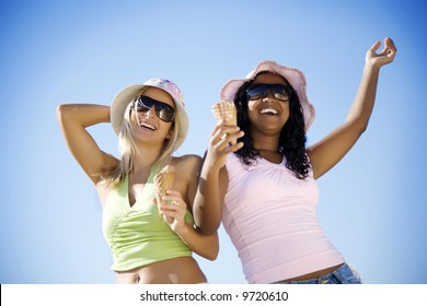 two girlseating ice-cream and laughing