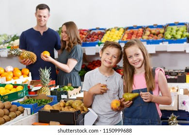 Two glad kids looking for fresh delicious fruits  in local supermarket with family