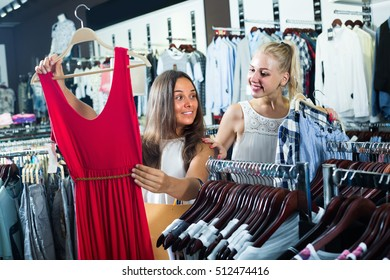 two glad young girls shopping new dress together in clothes shop