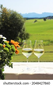 Two glaeses with whitewine on the balcony, beautiful bouquet with chrysanthemum on the left side, in the background alpine landscape, Allgäu, Bavaria