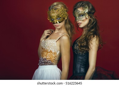Two glam gorgeous women, blonde and brunette, in golden and bronze masks wearing evening gowns standing on red background gazing intently with expressive eyes. Studio shot. Copy-space