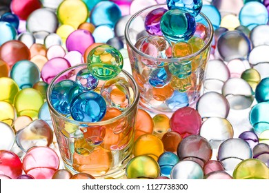 two glass beakers with hydrogel balls, transparent round shapes
