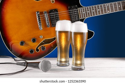Two glass beer and microphone near electric jazz guitar on white wooden desk. Blue background.