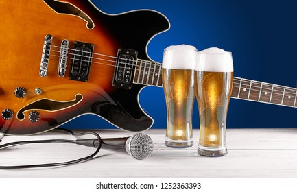 Two glass beer and microphone near electric jazz guitar on white wooden desk. Blue background