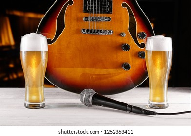 Two glass beer and microphone near electric jazz guitar on white wooden desk. Dark background.