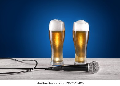 Two glass beer and microphone on white wooden desk. Blue background. Free space for text. Design