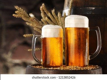 Two glass of beer on barley .stone wall on bakcground.Still life