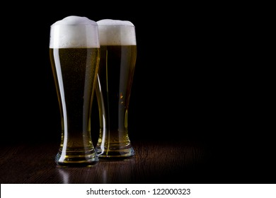 Two glass beer on a black and wooden table