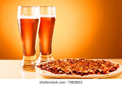 Two glass of beer and pizza over yellow background
