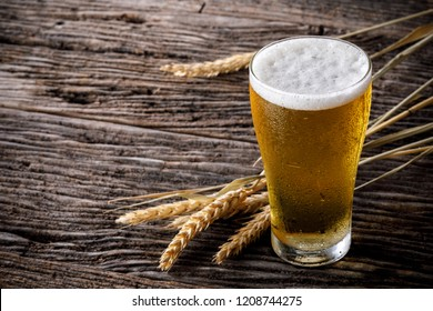 Two glass of beer with wheat on wooden table. Vintage style color effect