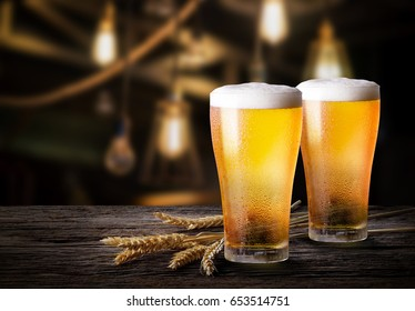 Two glass of beer with wheat on wooden table