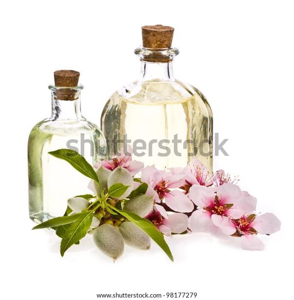 Zwei Glasflaschen mit Mandelöl und frischen Mandeln und Blumen einzeln auf weißem Hintergrund