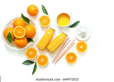 Two glass bottles of fresh orange juice, straws and oranges isolated on white background, copy space. Horizontal. Top view.