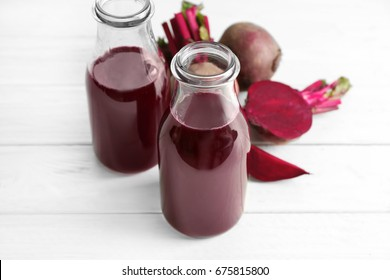 Two glass bottles with fresh smoothie and beets on wooden table