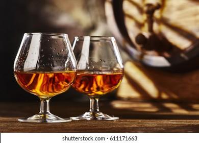 Two glass of Cognac and old oak barrel defocussed