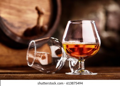 Two glass of Cognac and old oak barrel defocussed