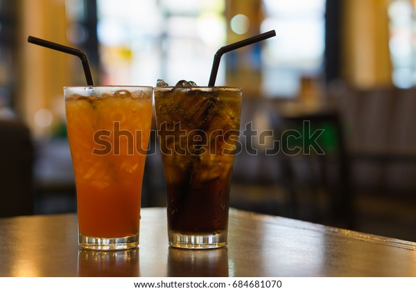 two glass of cola and orange with ice cubes on wooden table, selective focus and blurred background.