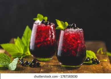 Two glass of cold ice black currant juice or cocktail with ripe berries and green leaves on dark wooden table. Alcohol or non alcohol summer fresh drink.