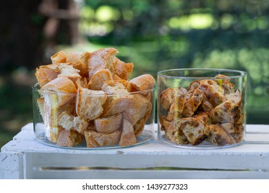 Two glass containers containing bits of bread and bits of bread with raisins