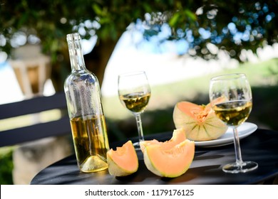 two glass of cool white wine with bottle outdoor in restaurant terrace during a sunny summer day