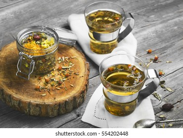 Two glass cups of  drink herbal tea. Glass jar on the board with dry herbal tea. Herbal tea is scattered on gray vintage wooden board.
