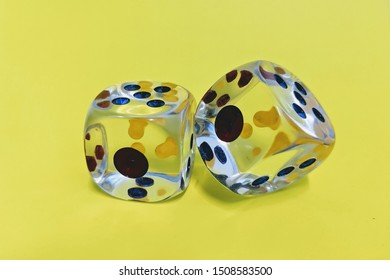 Two glass dice isolated on yellow background.