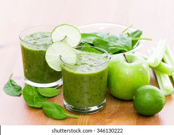 Two glass of green smoothie with spinach, celery, apple and lime on wooden surface, with slices of lime on the glass