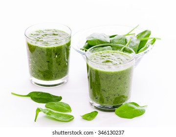 Two glass of green smoothie with spinach on white background, isolated