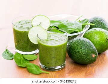 Two glass of green smoothie with spinach and avocado on wooden surface, with slices of lime on the glass