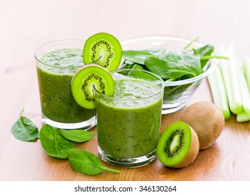 Two glass of green smoothie with spinach, celery and kiwi, on wooden surface, with slices of kiwi on the glass