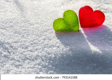 Two glass hearts on light background, green and red heart, white snow pattern, love and Saint Valentine day concept