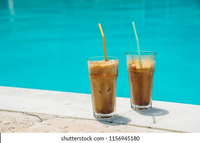 Two glass of iced frappe near the swimming pool.