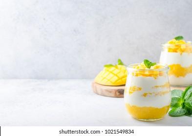 Deux bocaux en verre avec yaourt grec et mangue sur une table claire. Espace de copie, image horizontale, vue avant